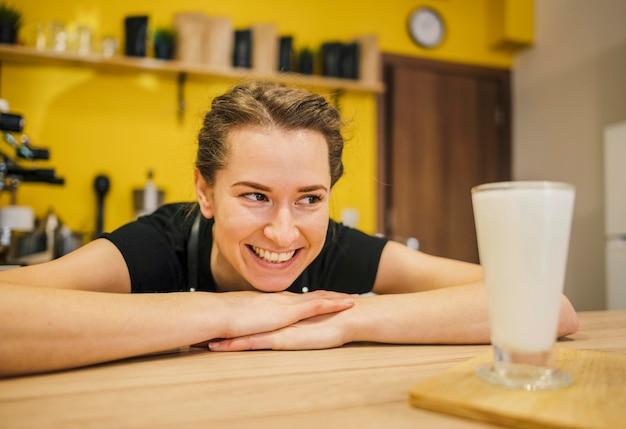 Vista frontal do barista sorridente, olhando para o copo de leite