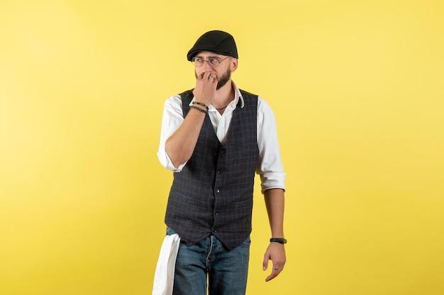 Vista frontal do barman do sexo masculino nervosamente pensando na parede amarela modelo noturno bebida trabalho clube trabalho masculino