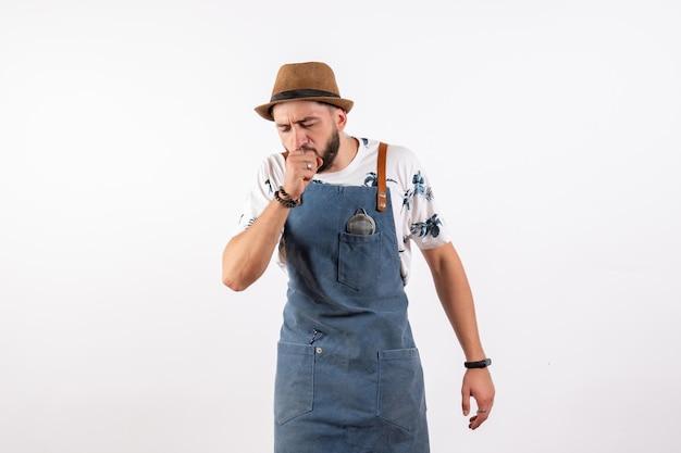 Vista frontal do barman do sexo masculino tossindo na parede branca modelo de trabalho de bebida alcoólica à noite em bar