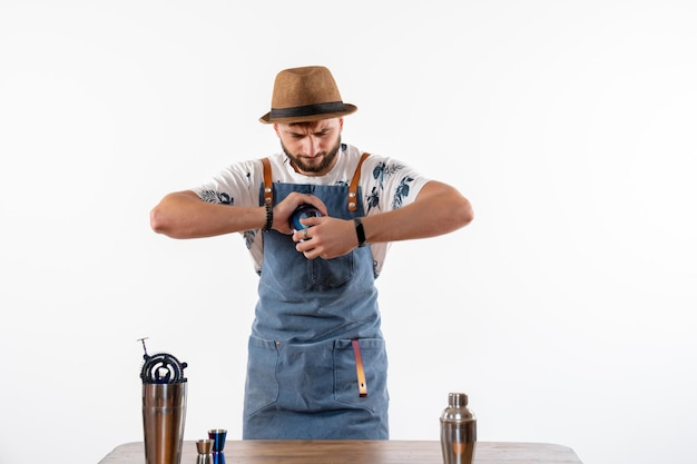 Vista frontal do barman em frente à mesa do bar fazendo uma bebida na coqueteleira na parede branca bar álcool trabalho noturno fruta bebida clube