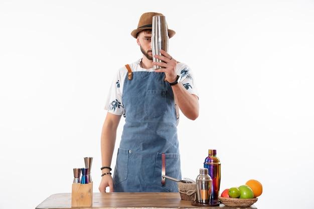 Vista frontal do barman em frente à mesa do bar preparando uma bebida em uma coqueteleira em uma parede branca.
