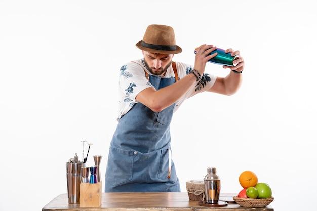 Vista frontal do barman em frente à mesa do bar preparando uma bebida na coqueteleira na parede branca bar álcool trabalho noturno fruta bebida clube