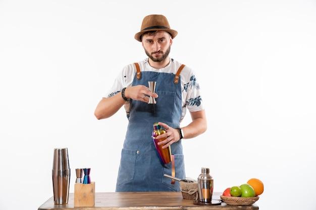 Vista frontal do barman em frente à mesa do bar preparando uma bebida na coqueteleira na parede branca clara.