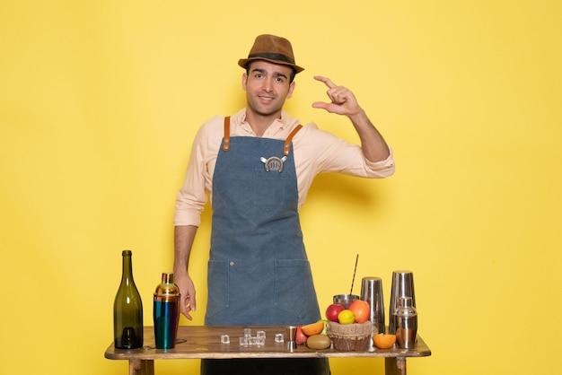 Vista frontal do barman masculino em frente à mesa com bebidas e coquetéis na parede amarela, bebida à noite, bar de álcool, clube de cores masculino