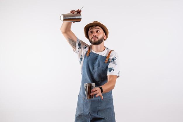 Vista frontal do barman segurando um coquetel na parede branca do clube noturno, bebida alcoólica, cor de trabalho