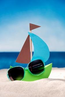 Vista frontal do barquinho de papel na areia da praia com óculos de sol