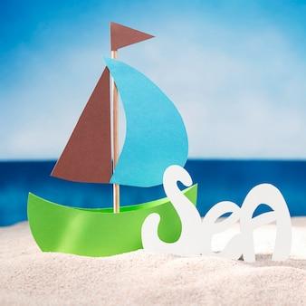 Vista frontal do barquinho de papel na praia