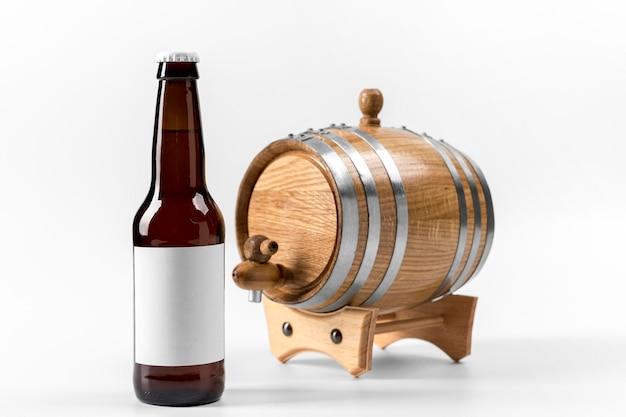 Vista frontal do barril de cerveja e garrafa com adesivo em branco