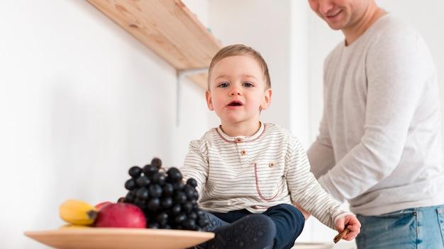 Vista frontal do bebê com o pai na cozinha