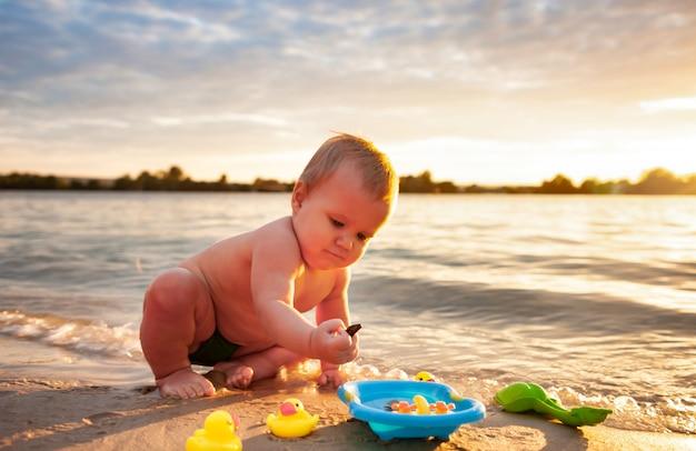 Vista frontal do bebezinho brincando com pequenos patos amarelos de borracha na pequena piscina azul, pôr do sol no fundo. criança atraente caucasiana se divertindo, sentado na areia da praia no mar, verão.