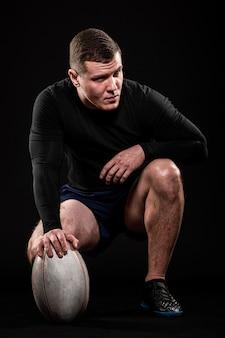 Vista frontal do belo jogador de rúgbi segurando uma bola