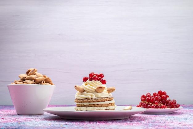 Vista frontal do bolo com creme junto com biscoitos e cranberries na superfície clara