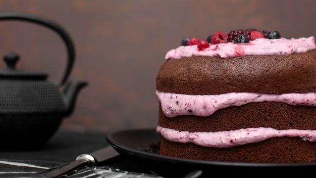 Vista frontal do bolo com faca e bule de chá