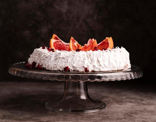 Vista frontal do bolo com glacê e frutas