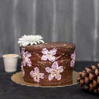 Vista frontal do bolo com pinha e flores