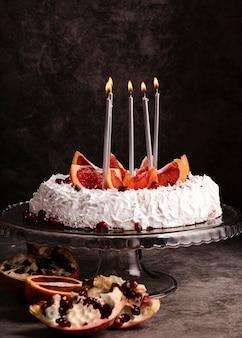 Vista frontal do bolo com velas e frutas