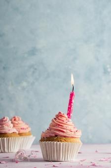 Vista frontal do bolo de aniversário com espaço de cópia e vela acesa