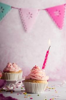Vista frontal do bolo de aniversário com festão e vela acesa