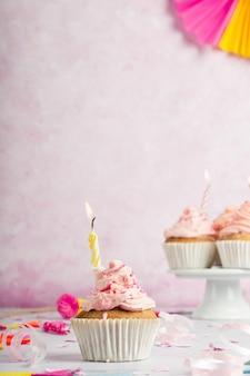 Vista frontal do bolo de aniversário com glacê e vela acesa
