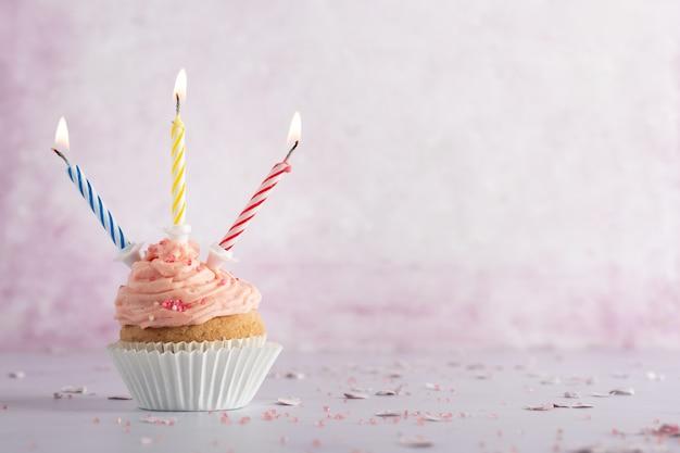 Vista frontal do bolo de aniversário com velas acesas e espaço de cópia