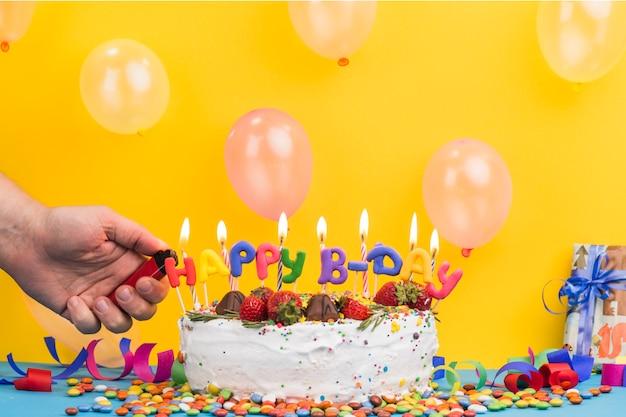 Vista frontal do bolo de aniversário mão acendendo velas