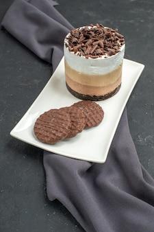 Vista frontal do bolo de chocolate e biscoitos em uma placa retangular branca xale roxo no escuro