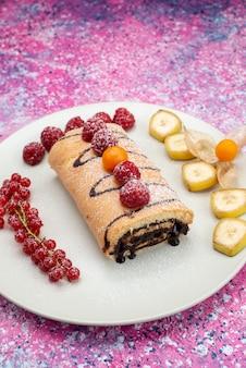 Vista frontal do bolo de chocolate junto com cranberries e frutas na superfície rosa
