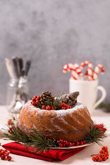 Vista frontal do bolo de natal com pinhas e bagas vermelhas