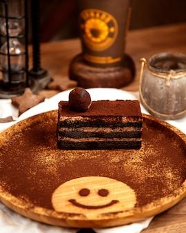 Vista frontal do bolo de trufa de sobremesa com cacau em pó em um quadro negro com uma carinha sorridente