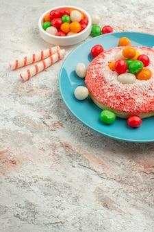 Vista frontal do bolo rosa gostoso com doces coloridos no fundo branco.