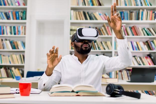 Vista frontal do bonitão barbudo de pele preta concentrada bonito no fone de ouvido de realidade aumentada, sentado na mesa na biblioteca e movendo as mãos na tela virtual ou livro