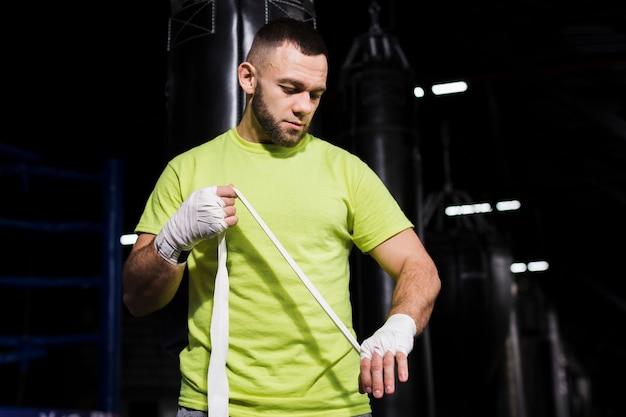 Vista frontal do boxer masculino, colocando proteção para as mãos