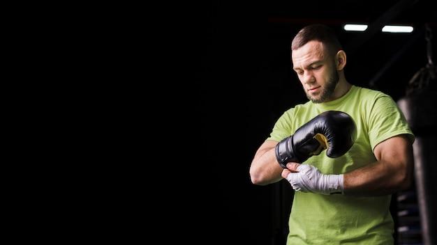 Vista frontal do boxer masculino em t-shirt com luvas de proteção e espaço para texto