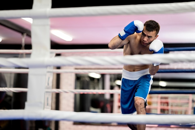 Vista frontal do boxer masculino praticando no ringue