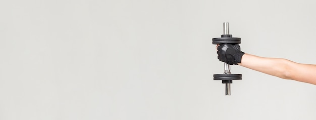 Vista frontal do braço da mulher segurando o peso com espaço de cópia