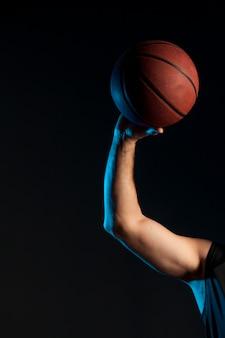 Vista frontal do braço do jogador de basquete, segurando a bola