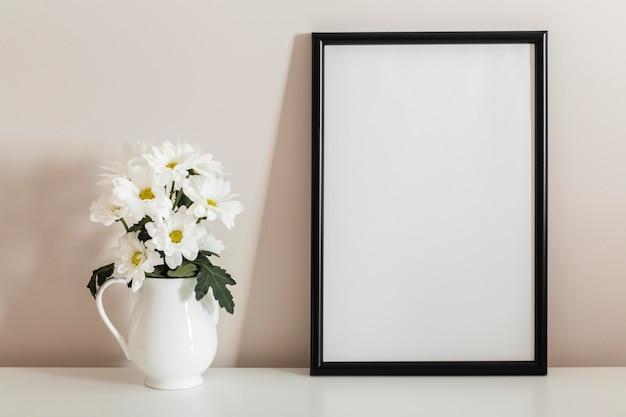 Vista frontal do buquê de flores brancas em um vaso com moldura vazia