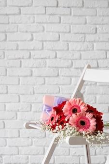Vista frontal do buquê de flores na cadeira branca