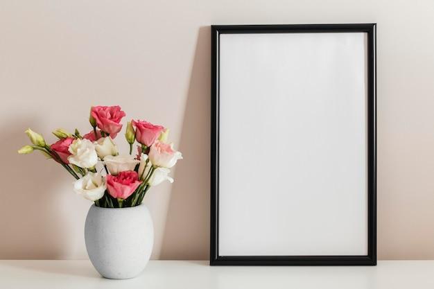 Vista frontal do buquê de rosas em um vaso com moldura vazia