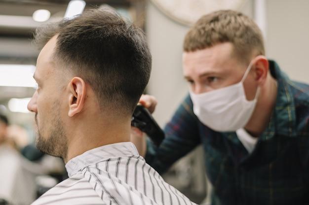 Vista frontal do cabeleireiro dando um corte de cabelo