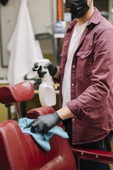 Vista frontal do cabeleireiro limpando a cadeira