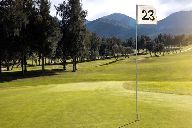 Vista frontal do campo de golfe com bandeira