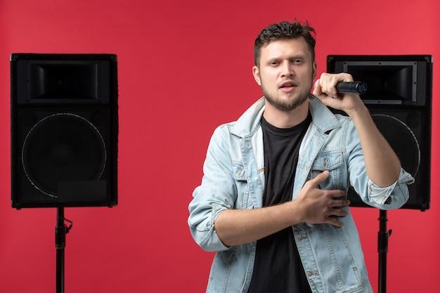 Vista frontal do cantor se apresentando no palco com o microfone na parede vermelha