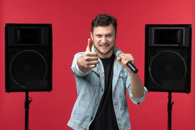 Vista frontal do cantor se apresentando no palco com sistema estéreo na parede vermelha Foto gratuita