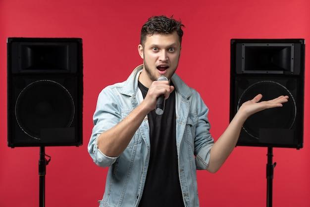 Vista frontal do cantor se apresentando no palco na parede vermelha