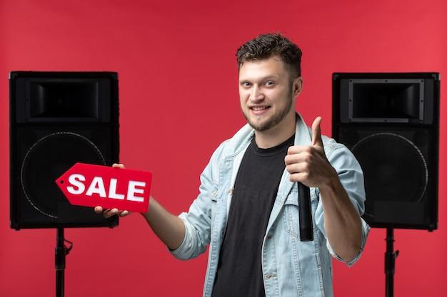 Vista frontal do cantor se apresentando no palco, segurando a escrita vermelha de venda na parede vermelha clara