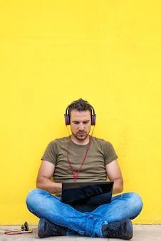 Vista frontal do cara atraente está sentado no chão com olhar moderno