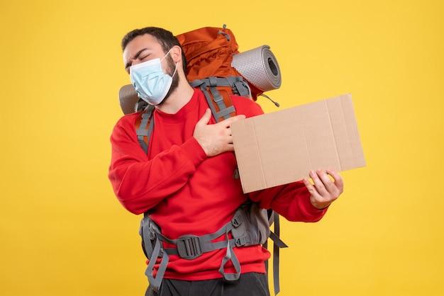 Vista frontal do cara do viajante usando máscara médica com mochila mostrando uma folha sem escrever sobre fundo amarelo