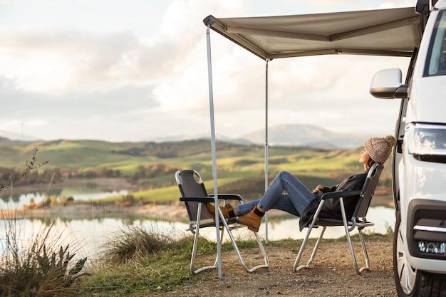 Vista frontal do carro de viagem perto do lago com mulher relaxando