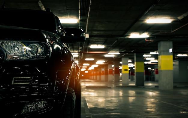 Vista frontal do carro preto estacionado no estacionamento subterrâneo de shopping center